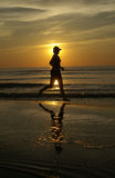 Sunset run. A woman runs (barefoot) on the beach during the golden sunset hour Royalty Free Stock Images