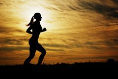 Sunset Runner. Beautiful young woman running in front of a sunset royalty free stock photo