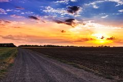 Sunset and rural road. Royalty Free Stock Images