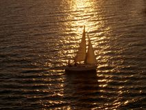 Sunset Sail. Sailboat returning to harbor after a day at sea. Caught in the rays of the sunset, backlighting the vessel Royalty Free Stock Photography