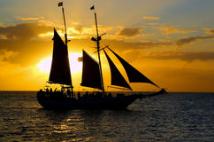 Sunset Sail II. Color photo of an ocean sunset with a tall ship silouhetted against orange and blue cloudy skies Royalty Free Stock Images