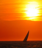 Sunset sailboat. Sailboat on horizon at sunset royalty free stock photo