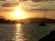 Sunset with sailboat Stock Photos