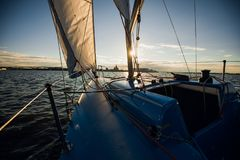 Sunset at the Sailboat deck while cruising sailing at opened sea or river. Yacht with full sails up at the end of windy. Day. Sailing theme - background royalty free stock image