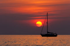 Sunset and sailboat. Sunset in Nai Harn beach and sailboat silhouette. Phuket, Thailand Stock Images