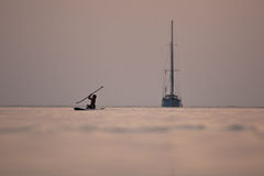 Sunset sailboat and young surfer Stock Photography