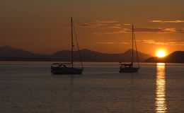 Sunset Sailboats. Sailboat silhouettes against an orange sunset sky Stock Image