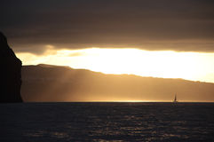 Sunset sailing in the Acores. Sailing near Ponta Delgada, in the Acores islands after a thunderstorm; sun rays are passing through the clouds Royalty Free Stock Photography