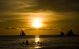 Sunset and sailing boats Stock Images