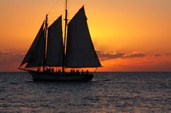 Sunset Sailing Party. A sailboat passes through the sunset line in Key West Stock Images