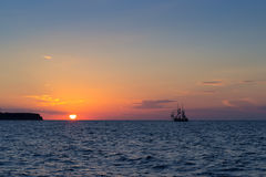 Sunset with sailing ship Stock Photography