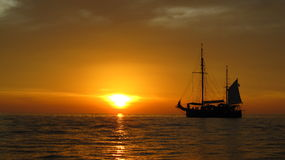 Sunset and sailing ship on the sea Royalty Free Stock Photo