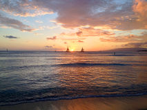 Sunset and sails. Sunset between 2 sails at Waikiki beach royalty free stock photography