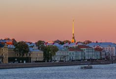 Sunset in Saint Petersburg over the Neva river with the view of the Palace Embankment and the Peter and Paul Fortress spire. Sunset in Saint Petersburg over the stock photo