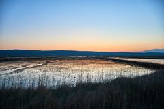 Sunset in the salt pans. Sunset on the salt pans walkway with grassland in the forefront royalty free stock photography