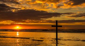 Sunset Salvation Beach. Dark cross on a beach with a wonderful sunset sky royalty free stock photo