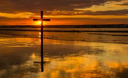 Sunset Salvation Waves. Dark cross on a beach with a wonderful sunset sky Stock Image