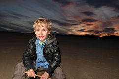 Boy with Sunset on the sand. Smiling young boy on the sand at sunset Royalty Free Stock Photography