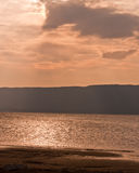 Sunset on the sand beach with hills and clouds. Warm sunset on a textured sand beach with clouds and hills in distance Stock Photos