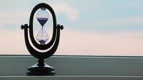 Sunset sand clock hand window background. Day light stock video footage