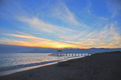 Sunset and a sandy beach in Antalya. In autumn, sun goes down to the mountains, sky is blue and gold with nice clouds, nobody around Royalty Free Stock Photo