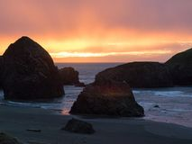 Sunset at sandy beach with sea stacks Stock Image