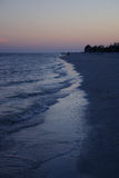 Sunset at Sanibel coast. Just at twilight the gentle waves reach the shore of the island accenting the silhouetted beach and foliage Stock Photography