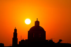 Sunset in Santorini. Blue dome of church as silhouette again the sunset in Santorini, Greece Royalty Free Stock Photography