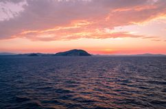 Sunset in Sardegna. An island is visible. Orange skies, blue water and waves stock image