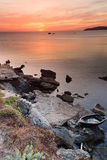 Sunset sardinia. Sunset on the rocks of Sardinia, a boat in the foreground, the background Capocaccia Stock Images