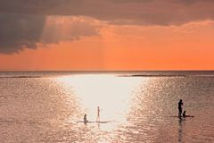 Sunset scene on coming thunderstorm background. Family silhouettes at sunset on ocean.A father with three children are paddling on stock images