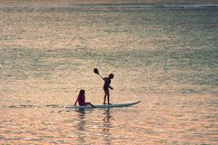 Sunset scene on  background. Two little girls silhouettes  are padddling stock photos