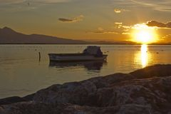 Sunset scene with fishing boat standing on water. Photo of sunset scene with fishing boat standing on water Stock Photos