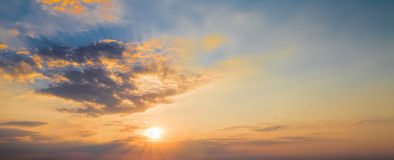 Sunset scene with sun fall and ray light, clouds in background, warm colorful sky Stock Photo