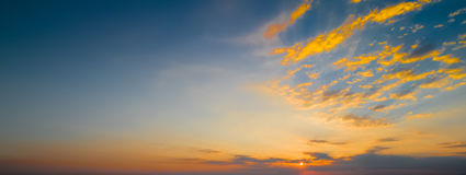 Sunset scene with sun fall and ray light, clouds in background, warm colorful sky Royalty Free Stock Photo