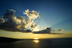 Sunset scenic ocean view in vast Aegean sea with beautiful abstract cloud and sun beam on shades of yellow and blue sky background. Santorini, Greece Royalty Free Stock Photography