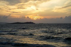 Sunset scenic powerful windy moving sea wave view with light reflection and beautiful shades of soft orange color sky background. Mykonos, Greece stock images