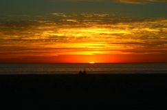 A couple watching sunset on the beach. Sunset in a glowing sky.  Wide angle shot Royalty Free Stock Photos