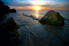 Sunset at the sea. With stones in the foreground Royalty Free Stock Photography