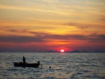 Sunset at sea. Sun setting on the horizon with a fisherman's boat in the foreground. Croatia. Europe Royalty Free Stock Images