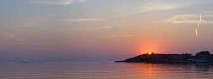 Sunset on sea. With cape in distance Stock Images