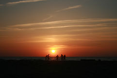 Sunset at the sea. Sunset and playing people on the sea Royalty Free Stock Photography