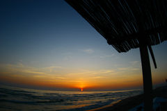 Sunset sea. Endless red sunset on the beach with tropical hut stock image