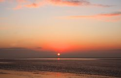 Sunset at sea. Orange sunset at the wadden sea in the Netherlands Royalty Free Stock Photo