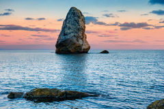 Sunset on the sea above big rocks Stock Images