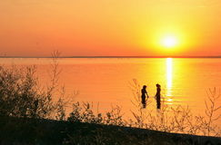 Sunset on the Sea of Azov, two female silhouette in water Royalty Free Stock Photography