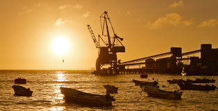 Sunset at the sea, back-lit dock, crane and boats Royalty Free Stock Photography