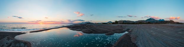 Sunset on sea beach, Cosenza, Italy. Beautiful sea sunset panorama with picturesque sky reflection in water. Ancient Cirella town ruins and mountain villages on Royalty Free Stock Photography