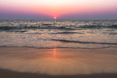 Sunset at sea beach. Scenic view from sand beach in Goa to beautiful sunset above the Arabian sea Royalty Free Stock Photo