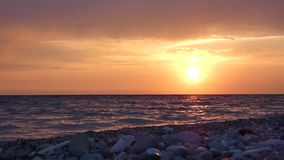 Sunset on sea beach in stormy day. Sun closely to the horizon, water waves breaking on pebbles and stones. Summer evening. Beautiful natural landscape stock footage